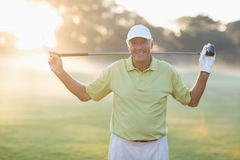 Portrait of smiling mature golfer carrying golf club. While standing on field Royalty Free Stock Photography