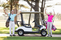 Portrait of smiling mature golfer couple with arms raised Stock Photo