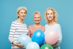 Portrait of smiling mature ladies with balloons. Portrait of smiling mature ladies in casual outfits standing together against blue wall and holding balloons royalty free stock images