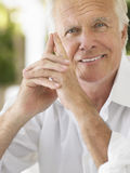 Portrait Of Smiling Mature Man. Closeup portrait of a smiling mature man with hands clasped Royalty Free Stock Photos