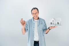 Portrait of smiling mature man with house model showing ok sign. On grey Royalty Free Stock Photography