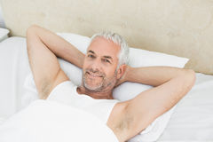 Portrait of a smiling mature man resting in bed Royalty Free Stock Images