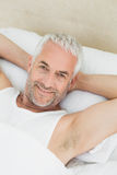 Portrait of a smiling mature man resting in bed Stock Photography