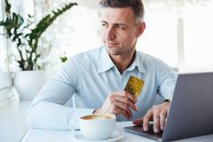 Portrait of a smiling mature man. Showing golden credit card and using laptop computer while sitting at the cafe table indoors Stock Image