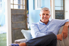 Portrait Of Smiling Mature Man Sitting On Sofa At Home Royalty Free Stock Images