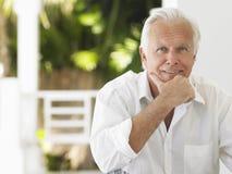 Portrait Of Smiling Mature Man. Portrait of a smiling mature man sitting on verandah stock image