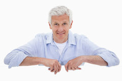Portrait of a smiling mature man standing behind blank panel Royalty Free Stock Photography