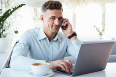 Portrait of a smiling mature man talking on mobile phone. And using laptop computer while sitting at the cafe table indoors Stock Photos