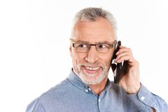 Portrait of smiling mature man talking on smartphone isolated. Portrait of smiling mature man in eyeglasses talking on smartphone and looking ae isolated over Stock Images