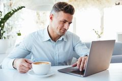 Portrait of a smiling mature man using laptop. Computer while sitting at the cafe table and drinking coffee indoors Royalty Free Stock Photo