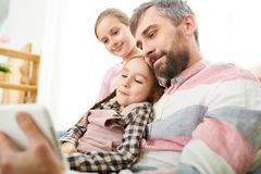 Happy Father with Two Daughters. Portrait of smiling mature men holding little girl while watching videos on digital tablet with two daughters Stock Image