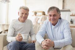 Portrait of smiling mature men sitting on sofa at home royalty free stock photography