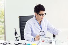 Portrait of a smiling mature scientist in a white coat with magnifying royalty free stock image