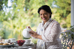 Portrait of smiling mature woman pouring tea in cup Stock Photo