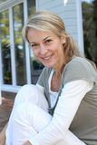 Portrait of smiling mature woman sitting outdoors Stock Photo
