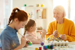 Mature Woman Painting Eggs for Easter stock photography
