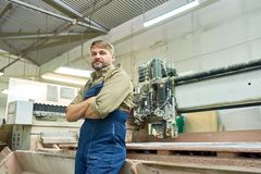 Mature Factory Worker Posing with Cutting Machine. Portrait of smiling mature workman posing with arms crossed and looking at camera by wood cutting machine in royalty free stock images