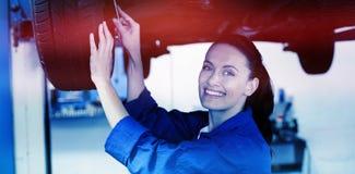Portrait of smiling mechanic adjusting tire. At repair garage Stock Images