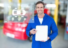 Portrait of smiling mechanic showing clipboard in garage stock images