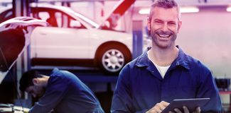 Portrait of smiling mechanic using tablet pc. While standing at garage Royalty Free Stock Photos