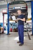 Portrait of smiling mechanic working on laptop Stock Photos