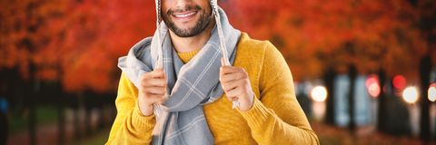 Composite image of portrait of smiling man holding wooly hat. Portrait of smiling men holding wooly hat against leaves on field amidst trees Stock Images