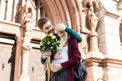portrait of smiling man surprising wife with bouquet of flowers stock photo
