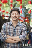 Portrait of Smiling Mid Adult Man with Arms Crossed in Nanluoguxiang, Beijing Stock Photography