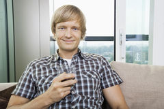 Portrait of smiling mid-adult man with glass of drink on sofa at home Royalty Free Stock Photo