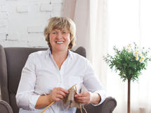 Portrait of a smiling middle age woman knitting on spokes Royalty Free Stock Photos