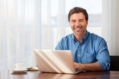 A portrait of a smiling middle-aged bearded man on a window background. His happy working home royalty free stock photo