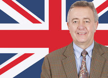 Portrait of smiling middle-aged businessman over British flag Stock Image