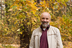 Portrait of a smiling middle-aged man. On the background of the autumn tree Royalty Free Stock Photography