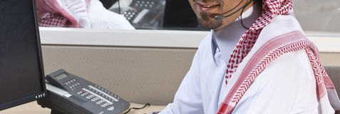 Portrait of a smiling Middle eastern employee with headphones on stock photography