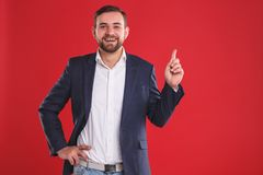 Portrait of smiling middle man pointing one finger stock images