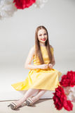 Portrait of smiling model in yellow dress with red lips Royalty Free Stock Photo