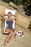 Portrait of smiling modern woman in swimwear in sunbed relaxing. Stylish getaway. Full length portrait of smiling modern woman in swimwear in a sunbed relaxing Stock Images