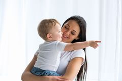 Portrait of smiling mother with adorable baby in hands pointing away. At home stock images