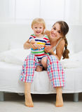 Portrait of smiling mother and baby in bedroom Royalty Free Stock Photography
