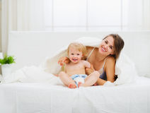 Portrait of smiling mother and baby in bedroom Stock Photo