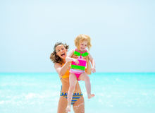 Portrait of smiling mother and baby girl on beach Royalty Free Stock Photos