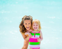 Portrait of smiling mother and baby girl on beach Stock Photo