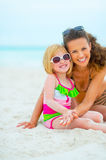 Portrait of smiling mother and baby girl on beach Stock Photography