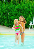Portrait of smiling mother and baby girl in pool Royalty Free Stock Photos