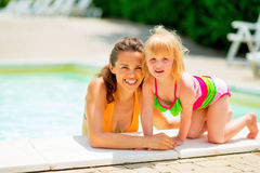 Portrait of smiling mother and baby girl at pool Royalty Free Stock Photo