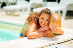 Portrait of smiling mother and baby girl in pool Stock Images
