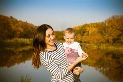 Portrait of smiling mother and baby on lake Stock Image
