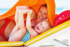 Portrait of smiling mother and baby laying on chaise-longue. On beach Stock Photos