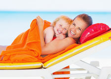 Portrait of smiling mother and baby laying on sunbed Royalty Free Stock Photography
