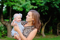 Portrait of smiling mother and baby outdoors Stock Photos